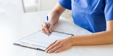 Nurse writing on notepad